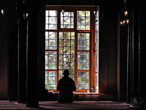 Мужчина молится у окна